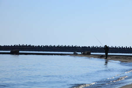 Stone breakwater seawall for protection of coast and fisherman silhouette Stock Photo - 25010990