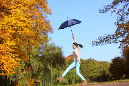 Happiness and freedom. Casual young woman girl jumping with blue umbrella in autumnal park, having fun outdoor photo