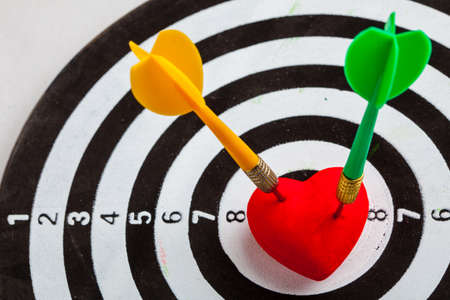 Closeup of black and white target with two dart in red valentine heart love symbol as bullseye. Skeet trap shooting sport in valentines day. photo