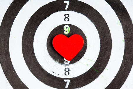 Closeup of old black and white target with red heart symbol bullseye as love background. Valentines day. photo