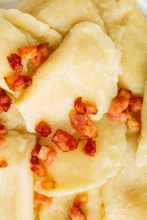 Closeup of dumplings sprinkled with pork scratchings as food background. Traditional polish (Poland) cuisine. photo