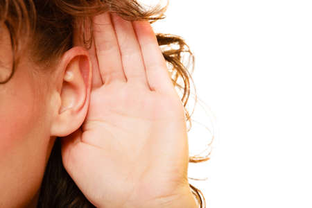 personas escuchando: Parte de la mano femenina mujer cabeza al o�do que escucha aislada sobre fondo blanco. Chismes Foto de archivo