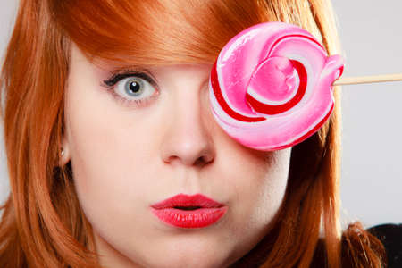 Funny young woman holding candy  Redhair girl with pink lollipop making fun  Studio shot  Sweets  photo