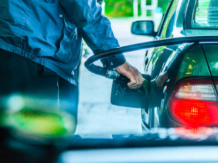 refilling: Male hand refilling the car with gas or petrol on filling station, holding a fuel pump outdoor Stock Photo