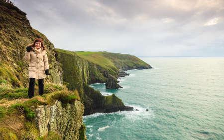 Irish atlantic coast  Woman tourist standing on rock cliff by the ocean Co  Cork Ireland Europe  Beautiful sea landscape natures beauty  photo