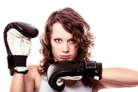 emancipation: Martial arts or emancipation idea concept. Sport boxer woman in black gloves. Fitness girl training kick boxing showing her power domination. Isolated on white background.