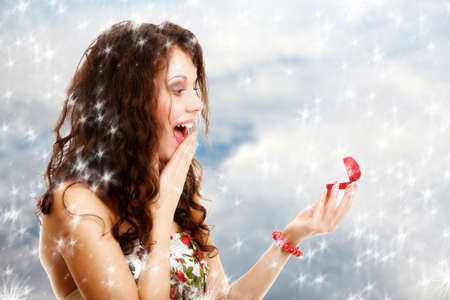 Attractive young woman opens a present heart shaped red box and is surprised happy by an engagement ring  Winter  photo