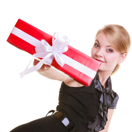 Happy smiling blond girl young woman in black dress holding big red christmas gift box with white ribbon  Holiday  Isolated on white  Studio shot  photo