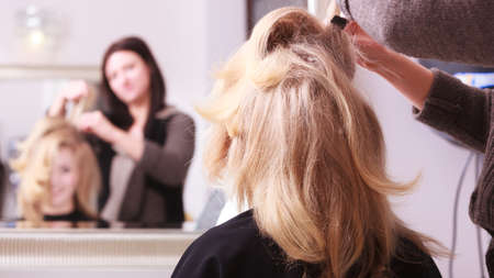 combing hair: Beautiful smiling girl with blond wavy hair by hairdresser  Hairstylist combing female client young woman in hairdressing beauty salon  Hairstyle