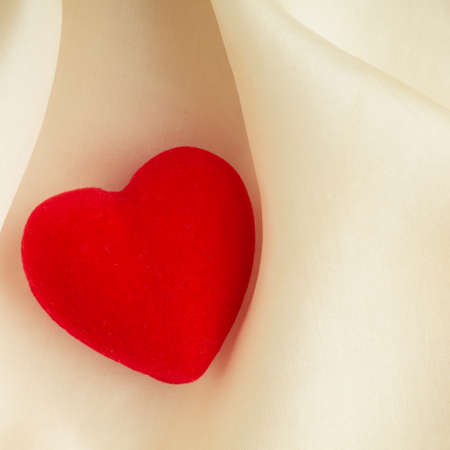 Valentine's day or wedding. Red wooden decorative heart on abstract white background luxury cloth silk or satin textile with copy space photo