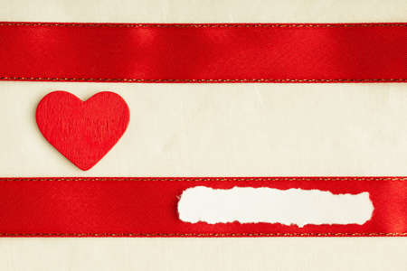 Valentines day background. Red satin ribbon with wooden heart on cloth. Copy space for text photo