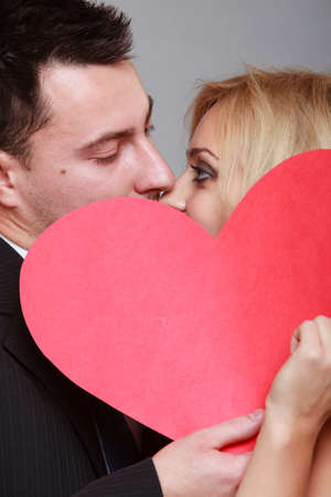 Wedding day  Happy blonde bride and groom kissing behind a red heart gray  photo
