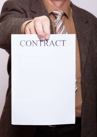 Business concept signing contract   Businessman holding blank empty paper sheet with sign contract and space for text  photo