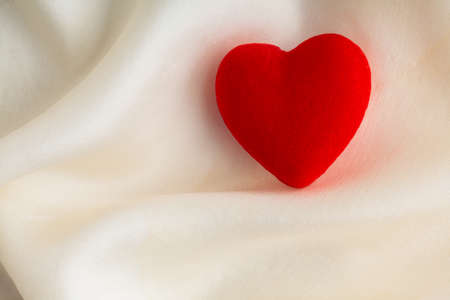 Valentine s day Red decorative heart on abstract white wavy folds cloth or textile elegant material photo