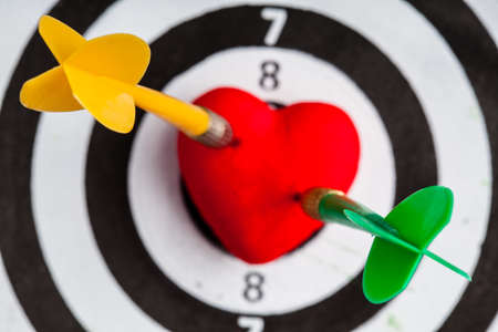 Heart dart stock photos royalty free heart dart images closeup of black and white target with two dart in red valentine heart love symbol as altavistaventures Image collections