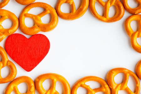 pretzels: frame of pretzels and red heart valentine love symbol on white background Stock Photo