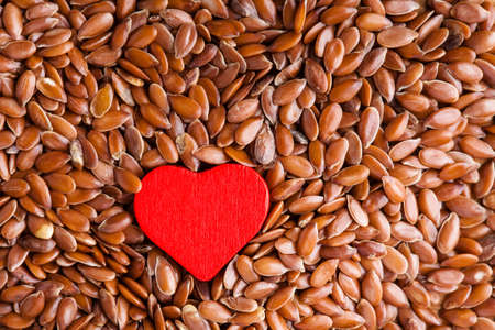 diet healthcare concept Brown raw flax seeds linseed as natural and red heart symbol Healthy food for preventing heart diseases Flaxseeds are full of omega-3 fatty acids
