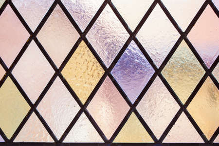 Stained glass with multi colored diamond pattern as pink violet tone photo