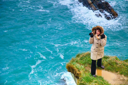 irish woman: Irish atlantic coast. Woman tourist standing on rock cliff by the ocean Co. Cork Ireland Europe. Beautiful sea landscape natures beauty. Stock Photo