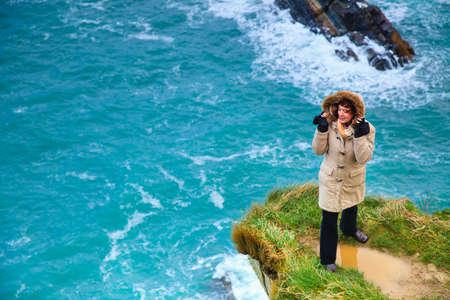 irish landscape: Irish atlantic coast. Woman tourist standing on rock cliff by the ocean Co. Cork Ireland Europe. Beautiful sea landscape natures beauty. Stock Photo