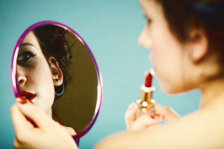 young woman preparing to party, girl styling hair with curlers applying make up red lipstick in hand looking at mirror retro style blue  photo