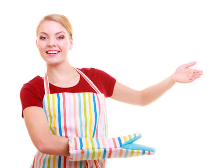 Happy housewife kitchen apron or small business owner entrepreneur shop assistant waitress making inviting welcome gesture pointing copy space isolated on white photo