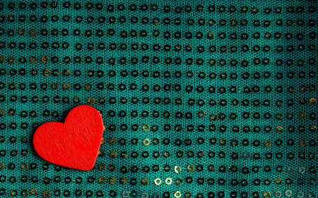 Valentines day . Red heart love symbol on blue green fabric textile material with golden shining sequins photo