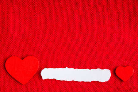Piece scrap of white paper blank copy space and hearts symbols of love on red fabric textile material . Valentines day. photo