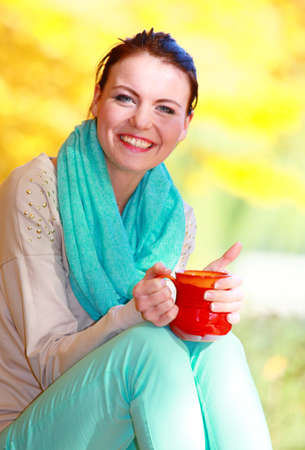 Happiness carefree and nature  Young happy woman relaxing in the autumn park enjoying hot drink coffee or tea, holding red mug with warm beverage  Yellow leaves  photo