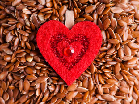 diet healthcare concept  Brown raw flax seeds linseed and red heart symbol  Healthy food  for preventing heart diseases  Flaxseeds are full of omega-3 fatty acids  photo
