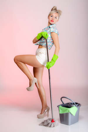 Full length sexy girl retro style with mop, woman housewife cleaner in domestic role. Traditional sharing household chores.  Pin up housework.  Pink background photo