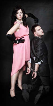 Detective theme. Retro style attractive couple, rich gangster in handcuffs and charming woman sexy detective spy with gun on black background