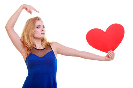 Red heart card. Love symbol. Beautiful woman hold Valentine day symbol pointing. Angry unhappy blonde girl in blue dress expressing tender feelings. Isolated studio shot photo