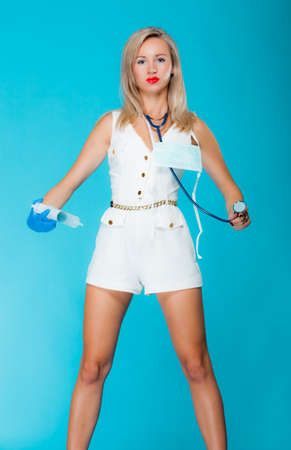 Funny sexy girl doctor nurse with syringe stethoscope. Medical person for health insurance. Vivid blue background photo