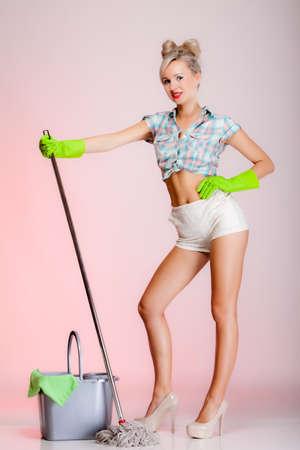 Plein sexy girl style rétro de longueur avec une vadrouille, femme ménagère plus propre dans le rôle domestique. Traditionnelles corvées partage des ménages. Pin up ménage. Fond rose Banque d'images - 25246276