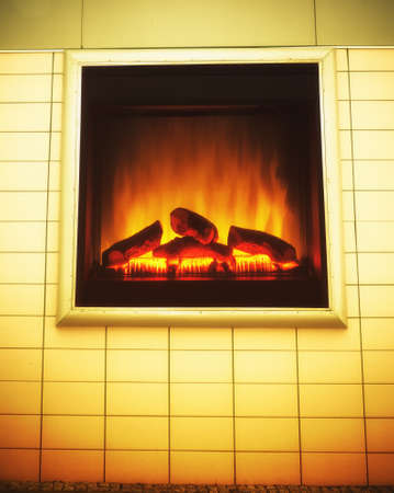 Closeup of electric artificial fireplace with orange fire flame interior as advertise billboard on wall  photo