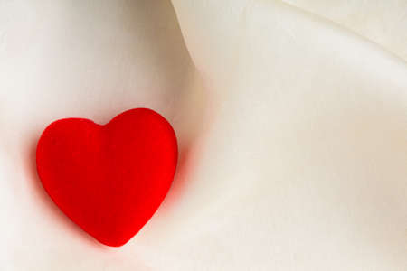 Valentines day or wedding. Red wooden decorative heart on abstract white background luxury cloth silk or satin textile with copy space photo