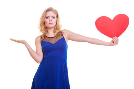 Red heart  Love symbol  Woman hold Valentine day symbol and showing empty hand palm with copyspace for product or text  Unhappy angry blonde girl in blue dress expressing tender feelings  Isolated studio shot photo