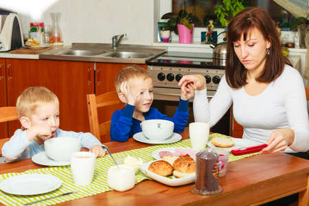 Happy family  Mother and blond sons boys kids children eating corn flakes and bread breakfast morning meal together at the table  Home  photo