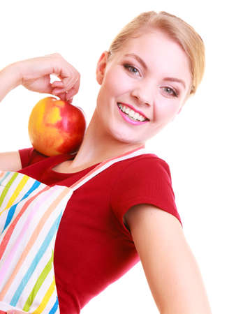 Happy housewife or chef in colorful kitchen holding red yellow apple healthy fruit isolated studio shot. Diet and nutrition. photo