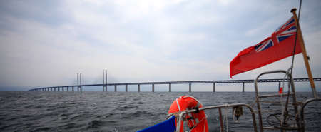 Oresundsbron  The Oresund bridge link between Denmark and Sweden, Europe, Baltic Sea  View from sailboat under UK british ensign  Overcast stormy sky  photo