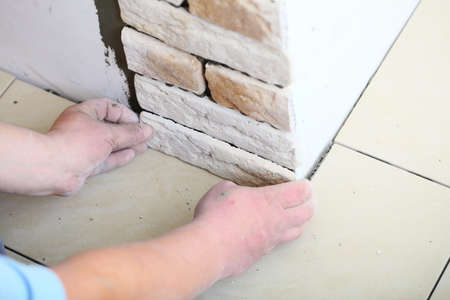 Renovation at home worker installing clinker tiles on a wall construction site