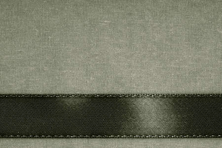 black ribbon: vintage background  Black ribbon on gray fabric cloth texture with copy space