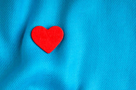Valentines day or wedding  Wooden decorative heart love symbol on blue wavy cloth textile background blank copy space photo