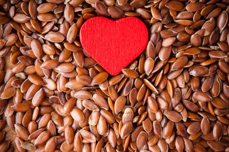 diet healthcare concept  Brown raw flax seeds linseed as natural background and red heart symbol  Healthy food  for preventing heart diseases  Flaxseeds are full of omega-3 fatty acids  photo
