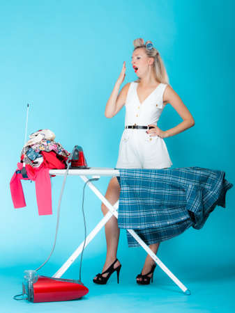 Full length sexy girl retro style ironing male shirt, tired woman housewife in domestic role  Traditional sharing household chores   Pin up housework   Vivid blue background photo