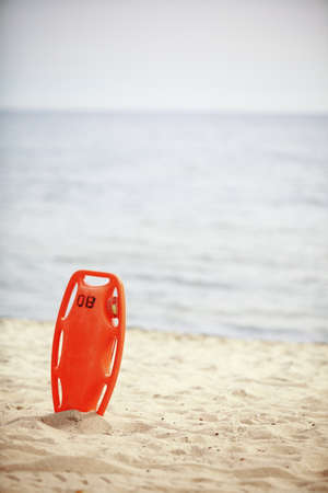 buoyancy: Beach life-saving  Lifeguard rescue equipment orange preserver tool, red plastic buoyancy aid in the sand