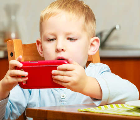 Happy childhood  Blond boy kid child playing with mobile phone at the table  Home  photo