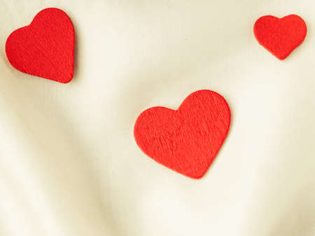 Valentines day background  Red decorative hearts on abstract white wavy folds cloth or textile elegant material photo