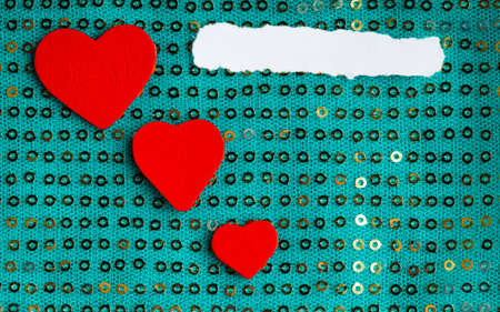 Valentines day background  white paper blank copy space red hearts love symbol on blue green fabric textile material with golden shining sequins photo